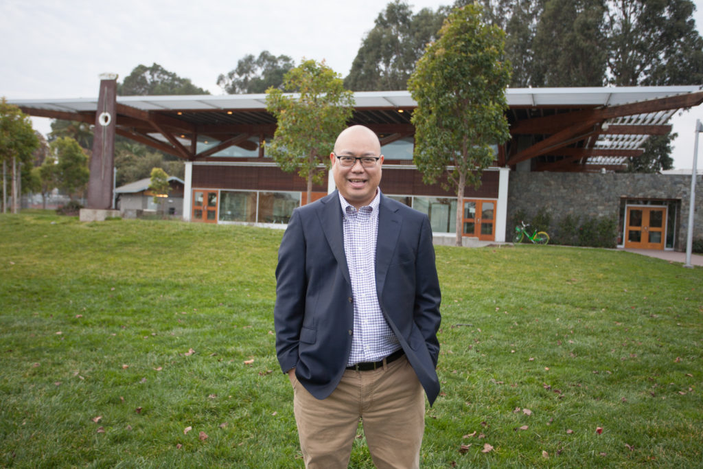 Mark Nagales standing in front of the Fernekes Building in Orange Memorial Park, South San Francisco, California. Photo: Kenni Camota, 2018.